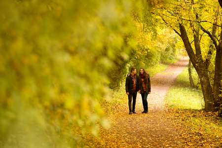 road of love: Lovers walking hand in hand in autumn park Stock Photo