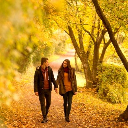 Lovers walking hand in hand in autumn park Standard-Bild