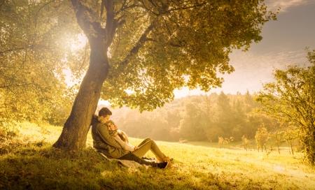 parejas felices: Amantes de la pareja debajo de un gran �rbol en el parque en oto�o