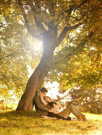 Passionate love in the park under a tree photo