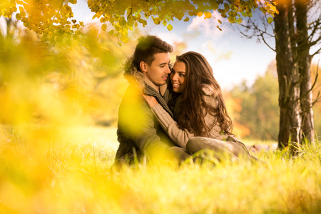 Passionate love under the tree in the autumn park photo