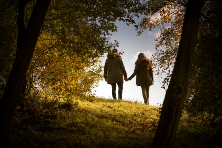 Lovers holding hands walking in the autumn park