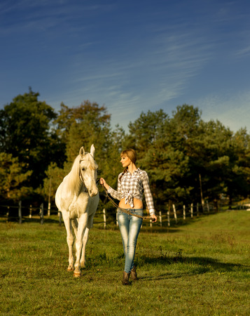 Young woman walking on a white horse at the ranch photo