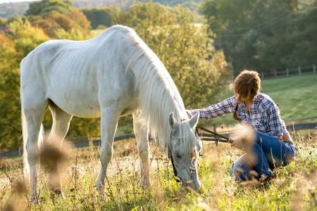 femme et cheval: Belle cow-girl avec son cheval blanc Banque d'images