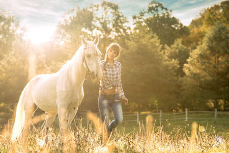 Young beautiful girl with a horse on the dry field photo