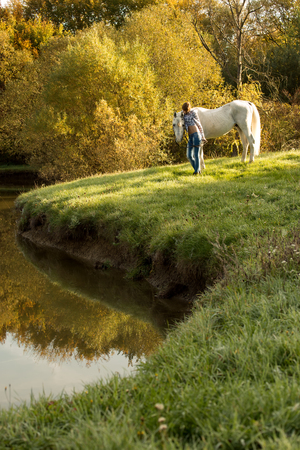 Young woman with horse in the lake photo