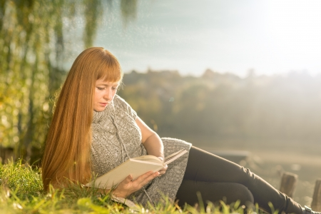 Beautiful-haired woman reading by the lake photo