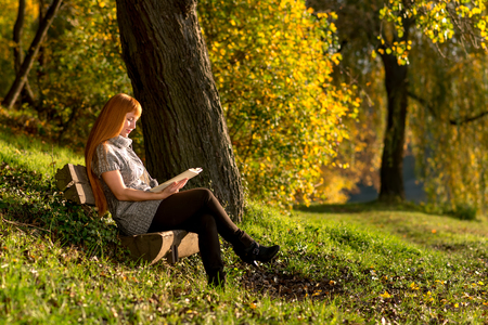 Woman read the book in autumn forest photo