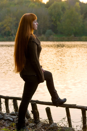 Beautiful-haired woman looking at the lake photo