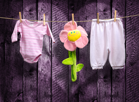 hang body: Baby girl clothes and a flower on a clothesline Stock Photo