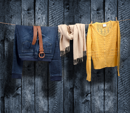 Women s clothing on a clothesline on wood background photo