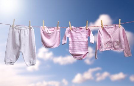 Clean baby girl clothes on the outdoor clothesline