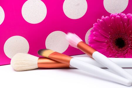 Makeup Brushes on polka dots pink background photo