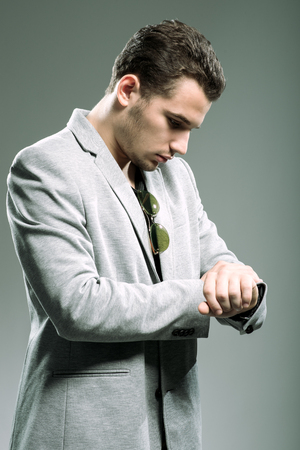 Handsome young businessman looking at his watch photo