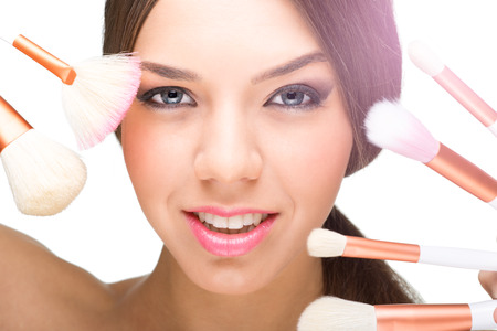 Beautiful model face with make-up brushes photo