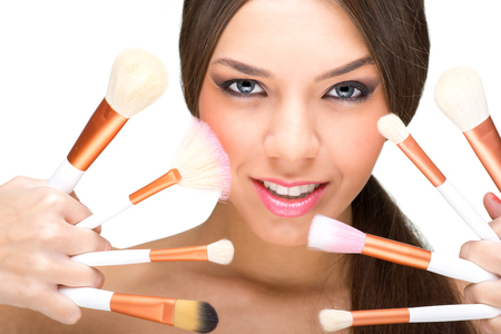 Beautiful model with perfect skin and makeup brushes photo