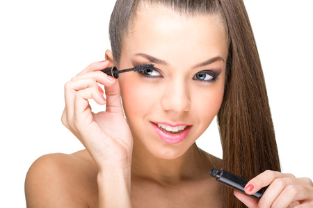 Beautiful fair skinned woman using mascara photo