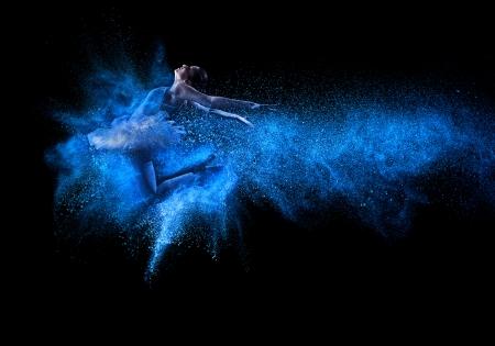 Mooie jonge danseres springen in blauw poeder wolk