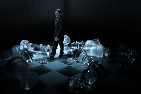 Businessman on a chessboard,walk from the capsized dummies photo