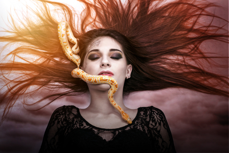 snake eyes: Woman lying on the floor with eyes closed, face the snake slither-awesome Stock Photo