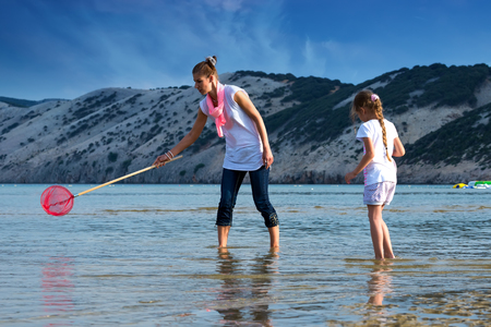 Mother and daughter on the beach fishing photo
