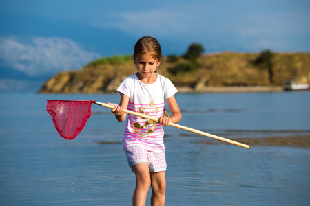 Beautiful little girl on the beach fishes Stock Photo - 24914548