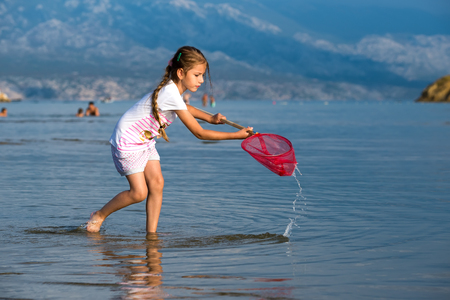 Beautiful little girl on the beach fishes Stock Photo - 24914735