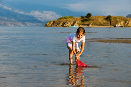 Beautiful little girl on the beach fishes photo