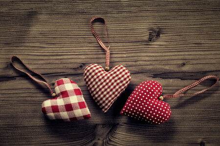 plano: 3 pieces of fabric hearts, polka dots , plaid, on wood background