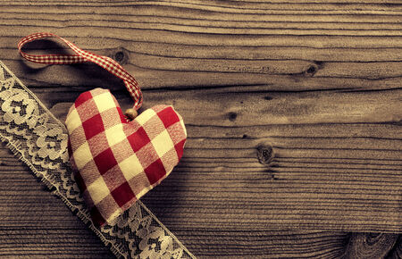 Checked fabric heart with lace wood background photo