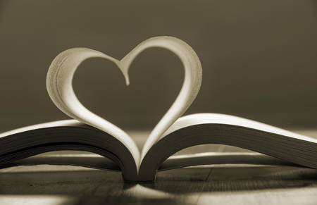 Open book with pages forming heart shape photo