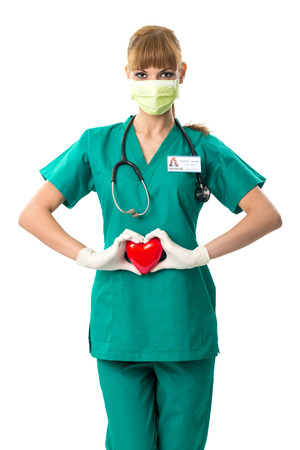 Pretty female surgeon holding a red heart photo