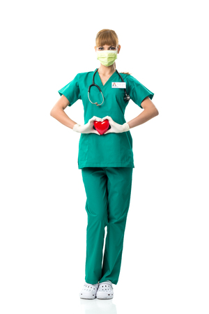 Beautiful female surgeon holding a red heart photo