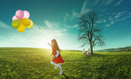 Happy girl running in a meadow with colorful balloons on a background of parents photo