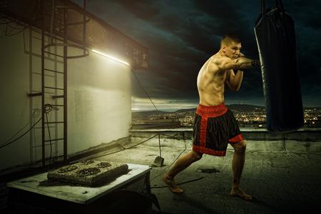 도시 위의 집의 상단에 젊은 남자가 권투 훈련,