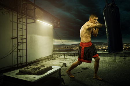 Young man boxing training , on top of the house above the city