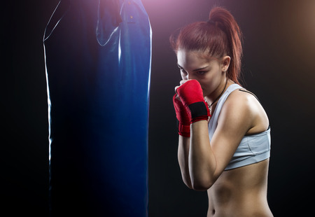 woman boxing gloves: Young woman boxing on a punching bag