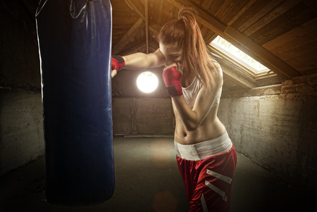 Young women boxing, hitting the boxing bag - on the attic  Imagens