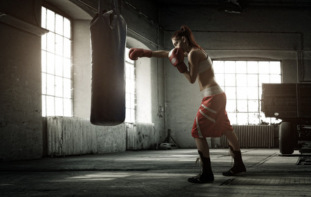 Young woman boxing workout in an old building photo