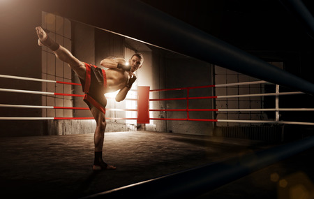 boxing sport: Young  man kickboxing in the Arena