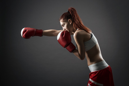 Boxing woman during exercise-gray background