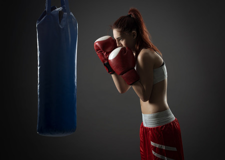 Boxing woman exercises with punching bag, on gray background  photo