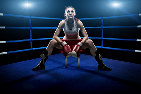 Boxing woman sitting alone in the boxing arena , surrounded by blue lights photo