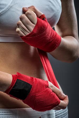 Boxing Frau bindet den Verband an seiner Hand, vor dem Training, Detail Foto Standard-Bild - 27698823