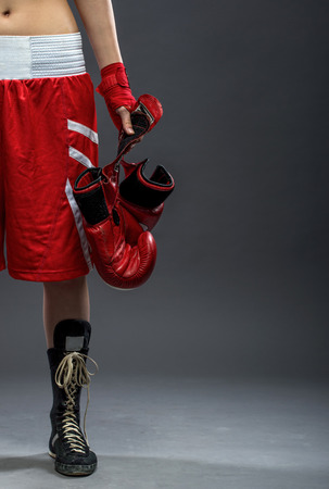 Boxing woman standing in box dress, holding boxing gloves - half body photo