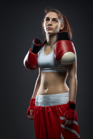 Boxing woman standing in dress boxing , boxing gloves on his shoulder photo