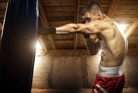 Young man boxing, exercise in the attic
