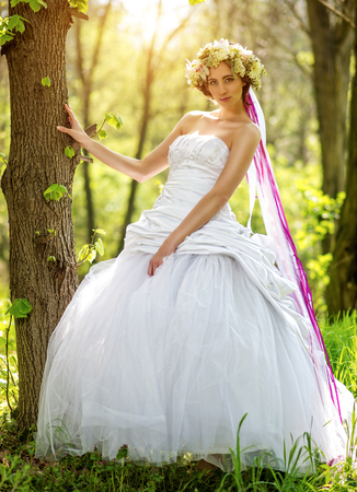 relying: Beautiful bride , flower tiara on her head , relying on the tree