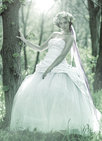 relying: Beautiful bride , flower tiara on her head , relying on the tree , monochrome