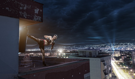 kick boxer: Young man boxing training , on top of the house above the city